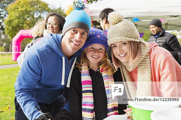 Porträt einer lächelnden  selbstbewussten Familie bei einer Wohltätigkeitsveranstaltung im Park