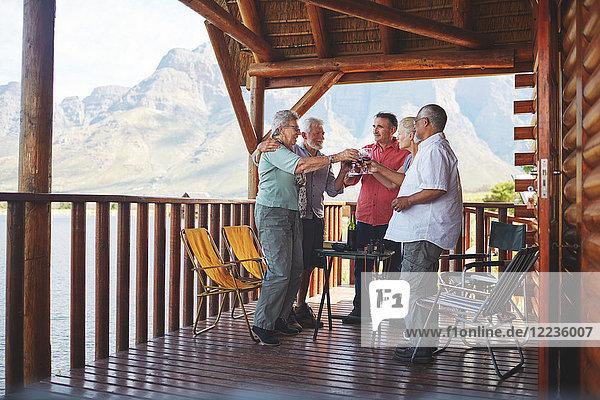 Aktive Seniorenfreunde toasten Weingläser auf dem Kabinenbalkon