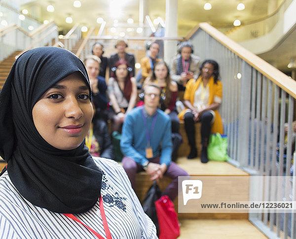 Porträt selbstbewusste Sprecherin im Hijab mit Publikum im Hintergrund