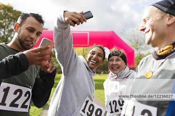 Glückliche Läuferfreunde nehmen Selfie mit Fotohandy beim Charity-Lauf im Park mit