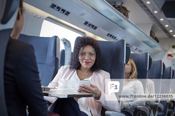 Portrait lächelnde  selbstbewusste Geschäftsfrau mit Smartphone im Personenzug