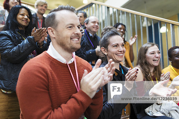 Lächelndes Konferenzpublikum klatscht