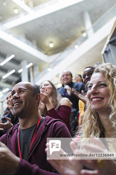 Lächelnde Menschen klatschen im Konferenzpublikum Lächelnde Menschen klatschen im Konferenzpublikum