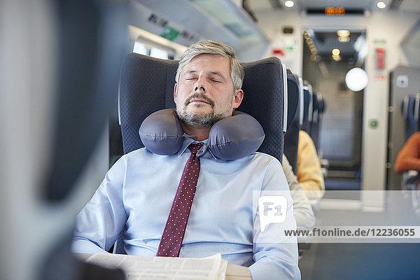 Müde Geschäftsmann mit Nackenkissen  der im Personenzug schläft