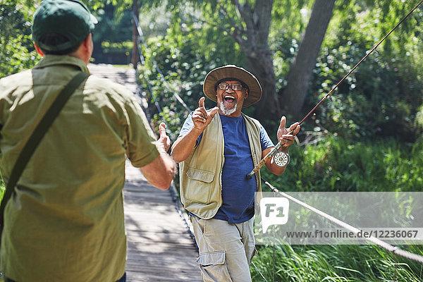 Spielerisch aktive Seniorenfreunde beim Angeln auf der Fußgängerbrücke