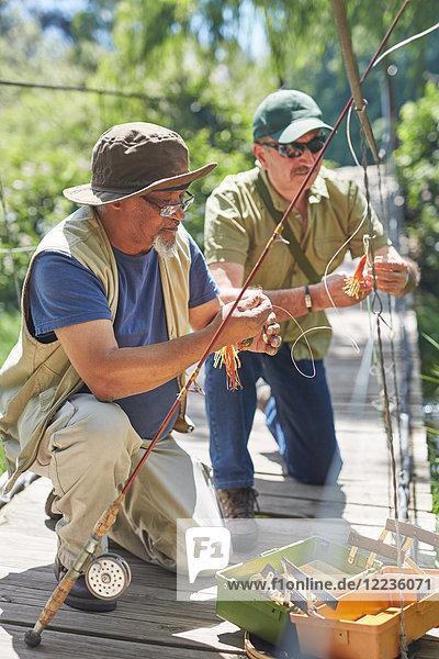 Aktive ältere männliche Freunde  die Angelschnüre vorbereiten