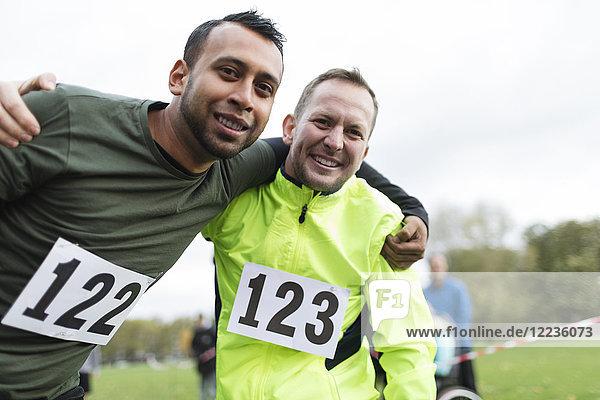 Portrait lächelnde männliche Marathonläufer umarmend