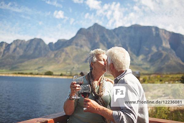 Romantisches  aktives Seniorenpaar küsst und trinkt Wein auf dem sonnigen Sommerbalkon am Seeufer.