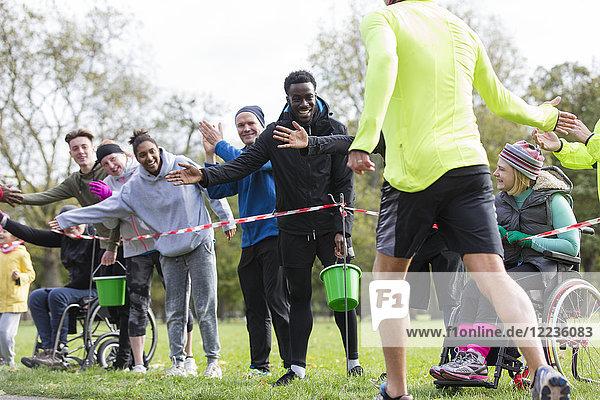 Zuschauer-High-Five-Läufer beim Benefizlauf im Park