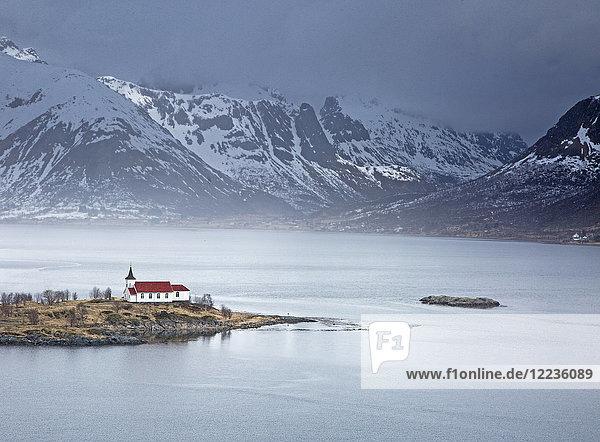 Abgelegene Kirche am Fjordufer unter verschneiten Bergen  Sildpoinesnet  Austvagoya  Norwegen