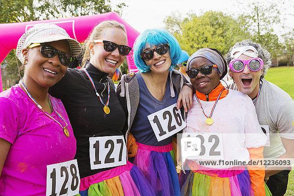 Portrait lächelnd  verspielte Läuferfreunde beim Benefizlauf im Park