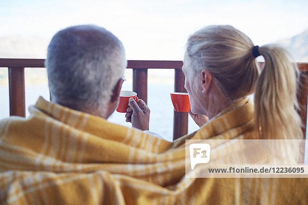 Gemütliches Paar in Decke gehüllt  Kaffee trinken auf dem Balkon