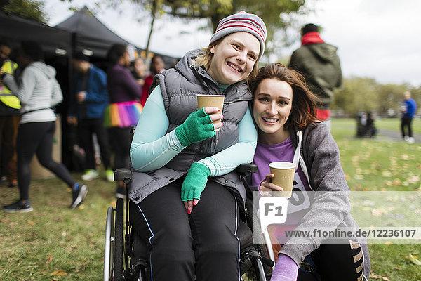 Portrait lächelnde Frau im Rollstuhl mit Freundin,  Trinkwasser beim Benefizrennen im Park