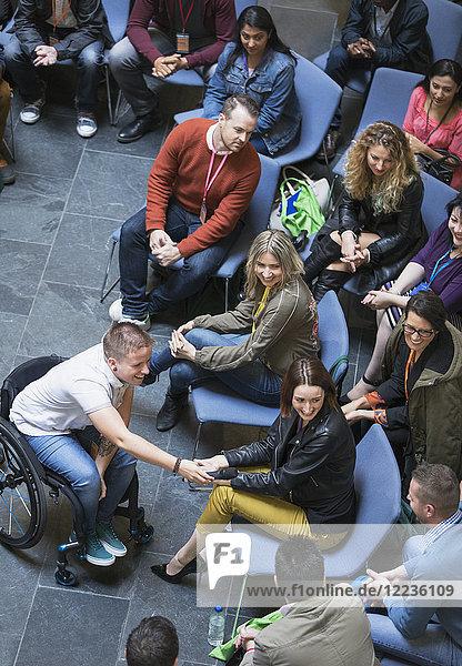 Sprecherin im Rollstuhl mit Mikrofon für das Publikum