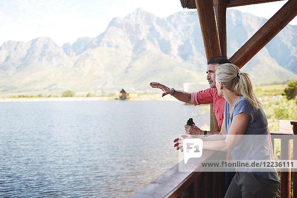 Paar mit Fernglas mit Blick vom Balkon auf den See