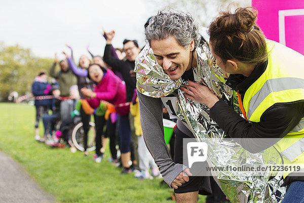 Frau wickelt Thermodecke um den erschöpften Läufer und beendet den Marathon.