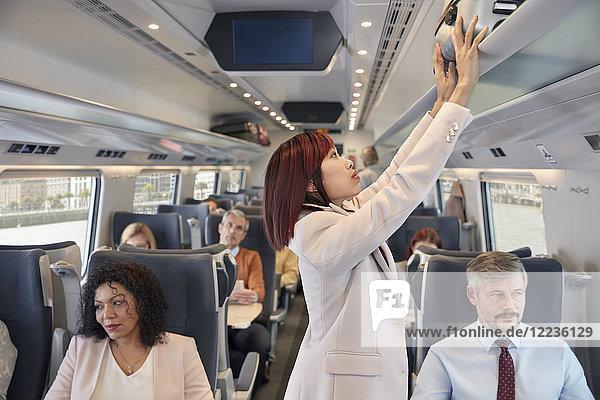 Geschäftsfrau verstaut Koffer im Fahrgastraum des Reisezuges