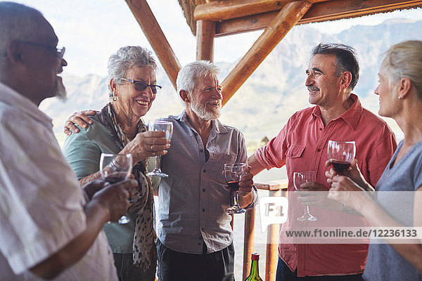 Glückliche aktive Seniorenfreunde beim Weintrinken auf dem Balkon