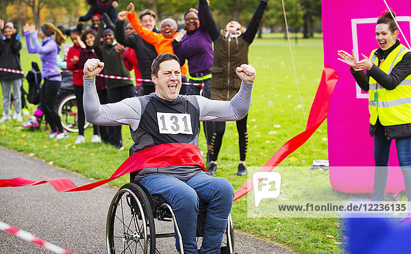 Begeisterter Mann im Rollstuhl überquert Ziellinie beim Charity-Rennen im Park