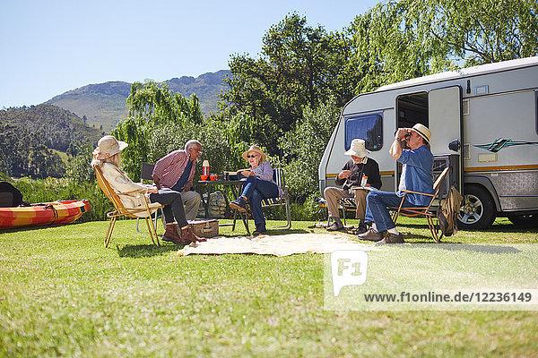 Aktive Seniorenfreunde entspannen sich vor dem Wohnmobil auf dem sonnigen Sommercampingplatz.
