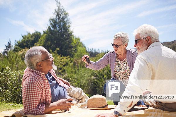 Aktive Seniorenfreunde mit Fotohandy  die das Sommerpicknick genießen