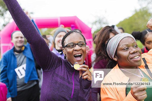 Begeisterte Läuferinnen mit Medaillenjubel  feiern beim Benefizlauf