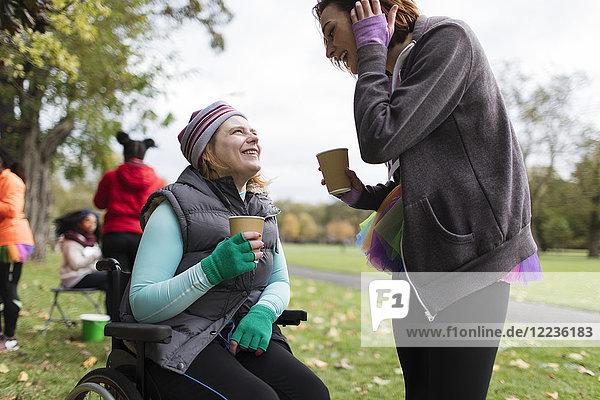 Frau im Rollstuhl im Gespräch mit Freundin im Park