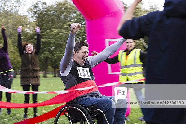 Enthusiastischer Mann im Rollstuhl überquert die Ziellinie des Charity-Rennens
