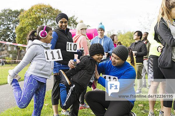 Familienläufer bereiten sich vor  strecken sich beim Benefizlauf im Park