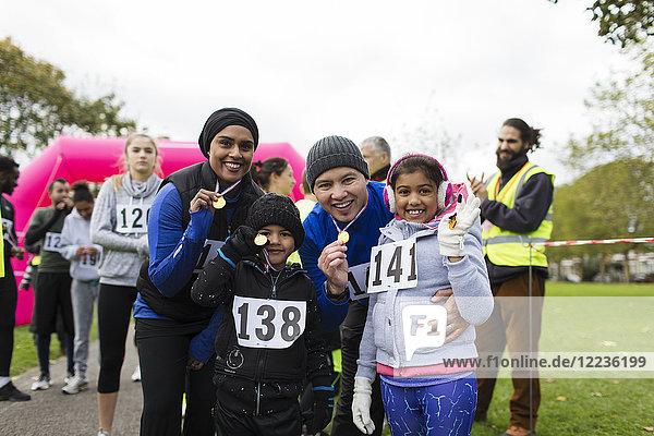Porträt einer selbstbewussten Familie mit Medaillen beim Benefizlauf im Park