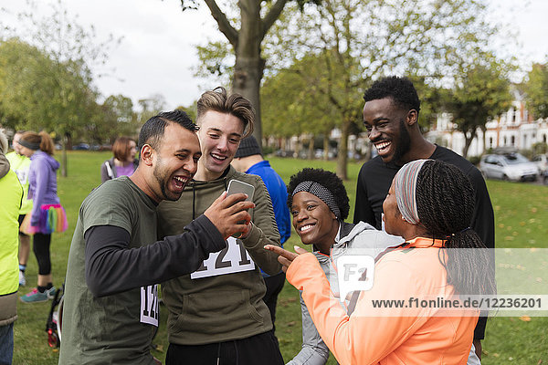 Freundschaftsläufer mit Smartphone beim Charity-Lauf im Park