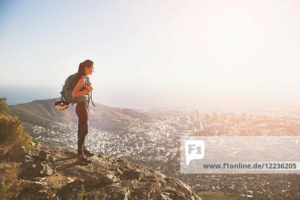 Weibliche Klettererin auf dem Hügel mit Blick auf die sonnige Stadt