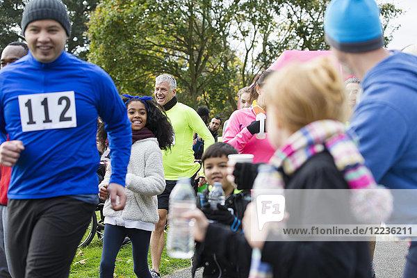 Zuschauer bieten Wasser für Läufer beim Charity-Lauf im Park an