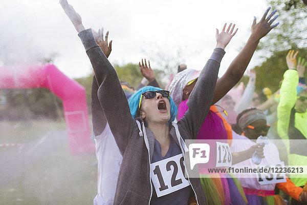 Enthusiastische Läuferinnen und Läufer werfen heiliges Pulver beim Charity-Rennen