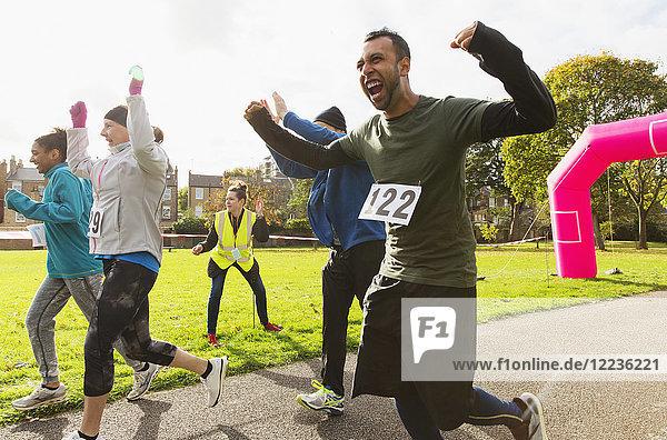 Überschwänglicher männlicher Läufer beim Charity-Lauf im sonnigen Park