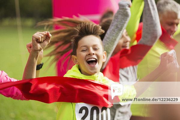 Enthusiastischer Läufer überquert die Ziellinie des Charity-Laufs