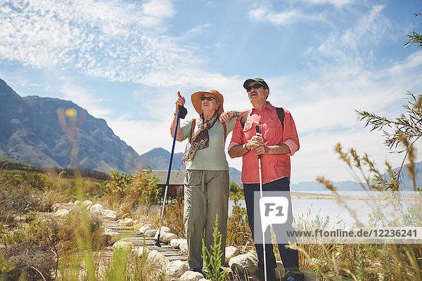 Aktives Seniorenpaar Wandern mit Wanderstöcken am sonnigen Sommerseeufer