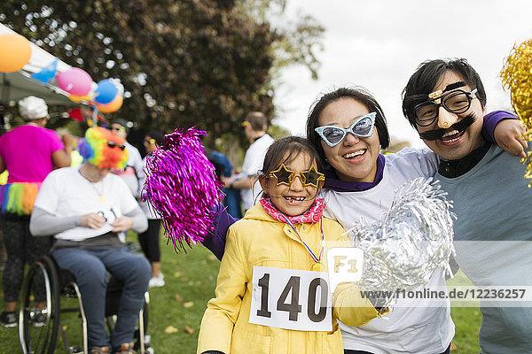Porträt einer verspielten Familie mit alberner Brille beim Charity-Lauf im Park