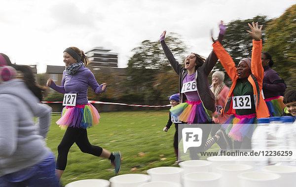 Enthusiastische Läuferinnen im Tutus jubeln  Laufen beim Charity-Rennen im Park