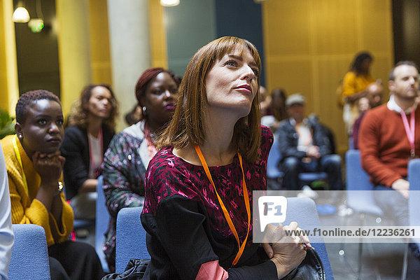 Aufmerksame  fokussierte Geschäftsfrau beim Zuhören im Konferenzpublikum