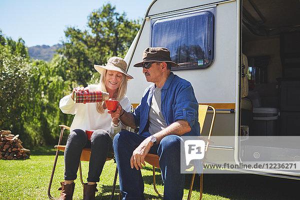Aktives Seniorenpaar trinkt Kaffee außerhalb des Wohnmobils auf dem sonnigen Sommercampingplatz.