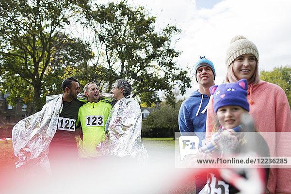 Männliche Marathonläufer in Thermodecke gewickelt im Park