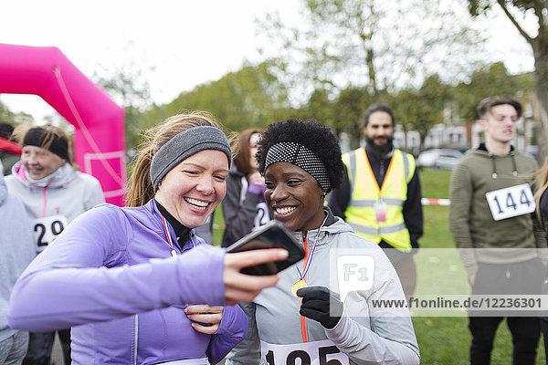 Läuferinnen mit Smartphone beim Charity-Lauf im Park