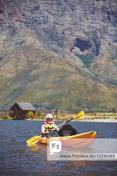Aktives Senioren-Kajakfahren auf dem sonnigen Sommersee
