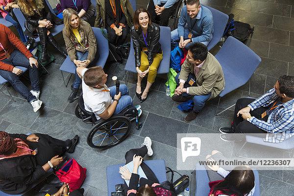Overhead-Lautsprecher im Rollstuhl mit Mikrofon im Gespräch mit dem Publikum