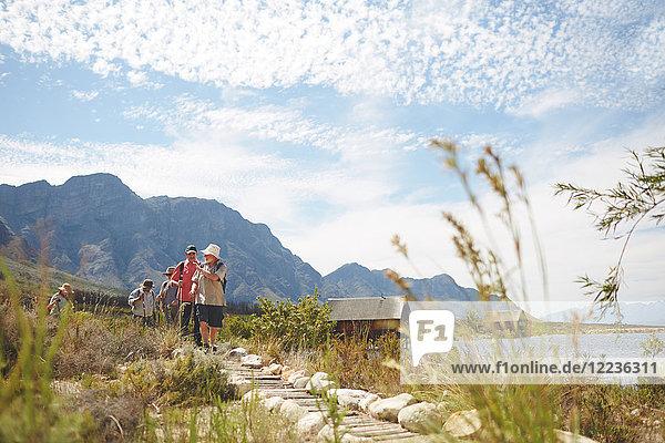 Freunde wandern auf einem Wanderweg entlang des sonnigen Sommersees