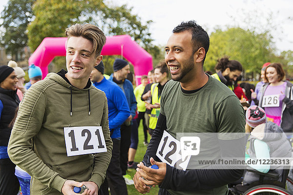 Männliche Läufer im Gespräch nach dem Benefizlauf im Park