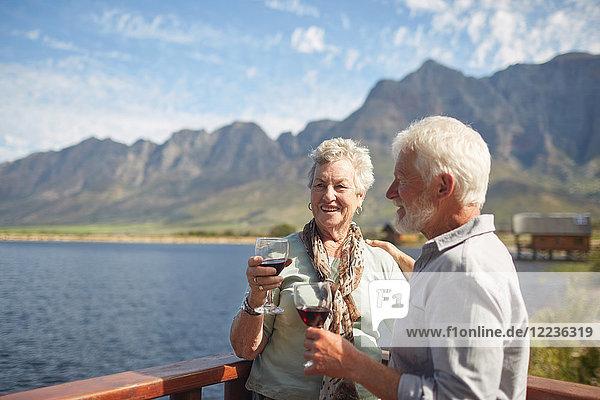 Lächelndes aktives Seniorenpaar trinkt Rotwein auf dem sonnigen Sommerseebalkon
