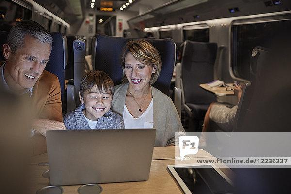 Familie mit Laptop im Personenzug bei Nacht