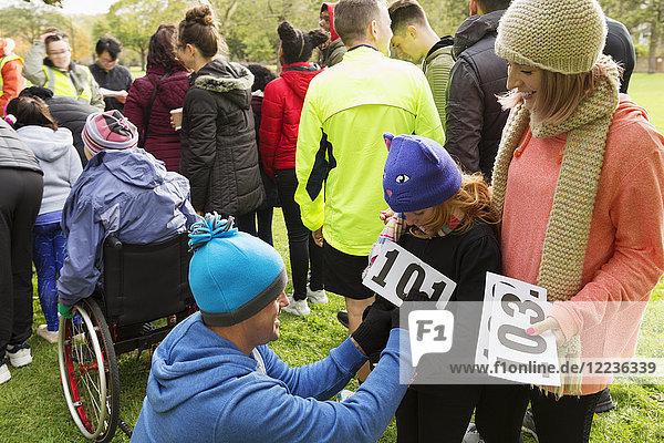Vater Läufer pinnt Marathon-Lätzchen auf Tochter beim Benefizlauf im Park
